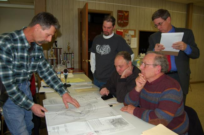 Gail Maholick/TIMES NEWS Rudy Wolff of Keystone Consulting Engineers, Kresgeville, left side of table, explains an Riverwalck Saloon exhibit to the Parryville Zoning Hearing Board, on right side are from left, standing, Scott Snyder, president; and…