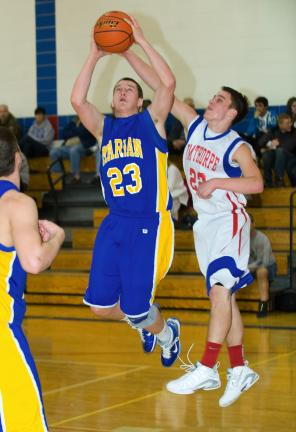 bob ford/times news Marian's Ryan Gimbi (23) goes up with a shot as Dane Ciavarella defends for Jim Thorpe.