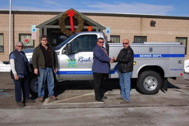 JOE PLASKO/TIMES NEWS Barry Messerschmidt (far right), sales representative for KME/Kovatch, Nesquehoning, hands the keys to a 2011 Ford F-250 4x4 truck for the Rush Township Sewer Department to Stephen W. Simchak, chairman of the township's board…