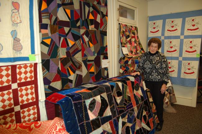 LINDA KOEHLER/TIMES NEWS Mary Taschler, a member of the Palmerton Area Historical Society, points out the beauty of several antique quilts and coverlets now featured at the Palmerton Heritage Center.