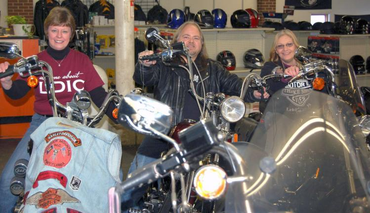 CHRIS PARKER/TIMES NEWS Lehighton Downtown Initiative Committee vice-president Brenda Koons, Thunder Mountain Motorcycle Club president Bud Stofik and Louise Stofik sit on cycles at the Stofik's shop in Lehighton. The LDIC has agreed to take over…
