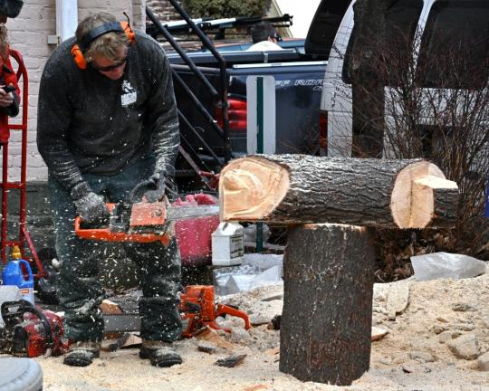 "VICTOR IZZO/SPECIAL TO THE TIMES NEWS Brian Ruth of ""Masters of the Chainsaw"" has wood chips flying as he carves another work of art from logs in front of the Mauch Chunk Opera House on Broadway."