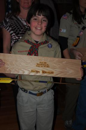 Brody Boehler holds his Arrow of Light plaque.
