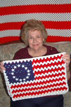 LINDA KOEHLER/TIMES NEWS Helen Snyder holds one of her crocheted American flags that she gives to area businesses to hang in their windows as a show of their patriotism. She makes them in different sizes, including the large afghan size like the one…