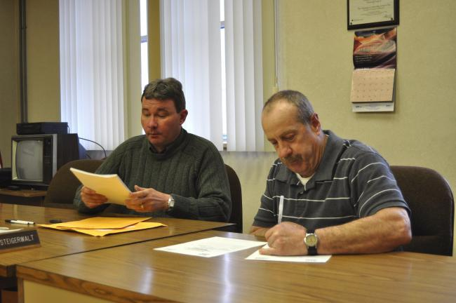DONALD R. SERFASS/TIMES NEWS Tamaqua Borough Manager Kevin Steigerwalt, left, and Public Works Director Rob Jones open bids Thursday for the Tamaqua Community Park Pool Project, aimed at diverting chlorinated water to a sewer instead of a waterway.