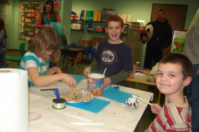"TERRY AHNER/TIMES NEWS Second-grade pupils Hannah Quinn (left) Zacary Reif (middle) and kindergartner Joshua Reif (right) display the homemade bird feeders they made in the ""Nature Center"" station."