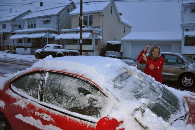 Ron Gower/TIMES NEWS Doreen Miller of Summit Hill removes about four inches of snow from her car before leaving for work this morning.