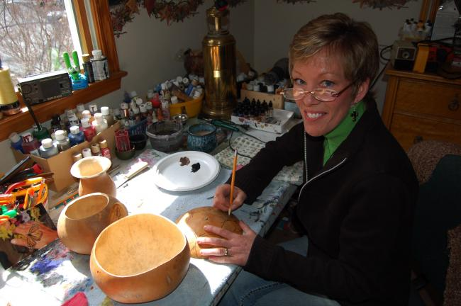 "LINDA KOEHLER/TIMES NEWS Cathy Wells is an admitted ""Gourd Lady."" Her passion is taking dried gourds and turning them into works of art. She is working on a gourd bowl with a butterfly design with a removable lid in her home workshop in Saylorsburg."