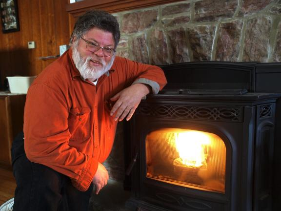 AL ZAGOFSKY/SPECIAL TO THE TIMES NEWS In front of his wood pellet burning stove, Stephen Kew-Goodale, executive director of the Weatherly Institute For Robotics and Engineering discusses his upcoming Alternative Energy Solutions workshop.