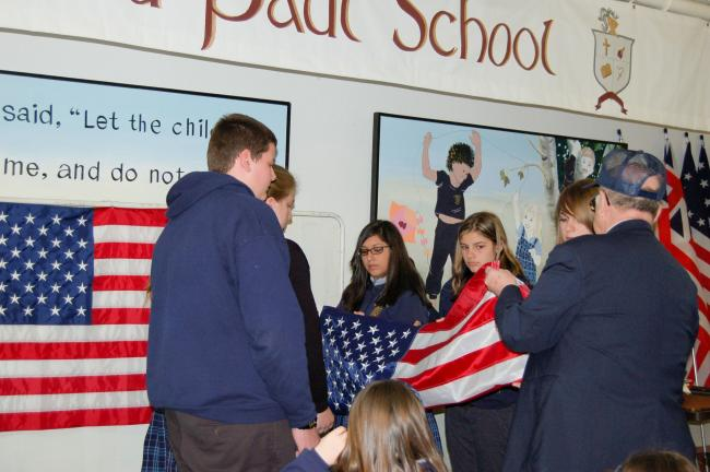 Gail Maholick/TIMES NEWS Stanley Jaroszewski, senior executive officer, teaches the eighth grade students at Ss. Peter and Paul Catholic School, Lehighton, how to correctly fold a flag.