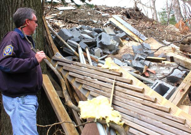 Dutch Hill resident Tom Hartz Jr. looks over dumped construction debris that someone recently piled at the future site of the Dutch Hill Playground in Tamaqua.