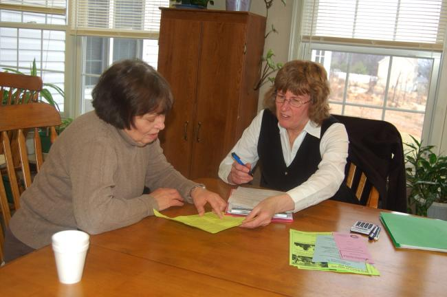 TERRY AHNER/TIMES NEWS Sally Watson (left) of Lehighton receives instruction from K. Tucker Landon, a volunteer with RSVP, as part of the BenefitsCheckUp program Wednesday at the Village at Palmerton.