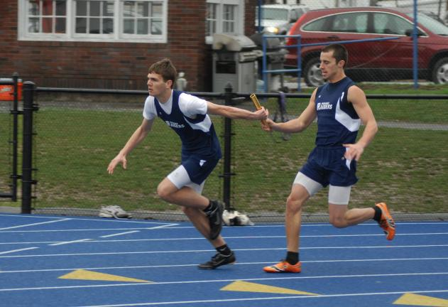 ron gower/times news Eric Herzog, front, takes baton from Tamaqua teammate Zach Lakitsky in 400 meter relay race.