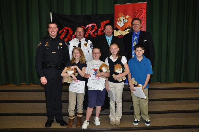 AMY MILLER/TIMES NEWS Fifth grade L.B. Morris Elementary School students Grace Kenna, Mikki Bernhard, Mackenzie Rosenberger, and Tucker Mertz, all front, were named this year's D.A.R.E. essay winners during the D.A.R.E. graduation on Friday morning…