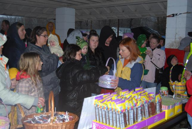 RON GOWER/TIMES NEWS Ashley Urban, representing Boyer's Market in Lansford, hands out plastic Easter eggs to youngsters during annual Easter festivities staged by Lansford Alive. The event was held inside the Lansford Pool pavillion because of heavy rain.
