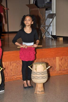 AMY MILLER/TIMES NEWS Tamyra Green, a second grade student at Penn-Kidder Elementary and a SHINE student, performs on an African drum during the SHINE multicultural night at the school recently.