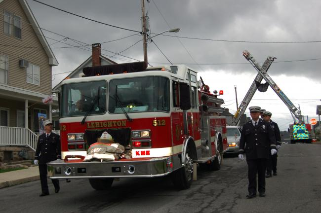 "Gail Maholick/TIMES NEWS Lehighton Fire Truck 512 passes through the arch made by two aerial fire trucks during the funeral procession for Lehighton Fire Chief John ""Jack"" Kuller Jr. on Wednesday."