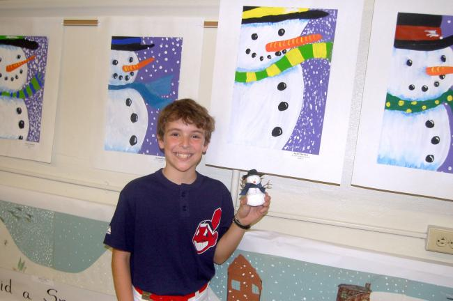 TERRY AHNER/TIMES NEWS Michael Martinez, a fourth-grade student at St. John Neumann Regional School, proudly displays his snowman painting and pin.