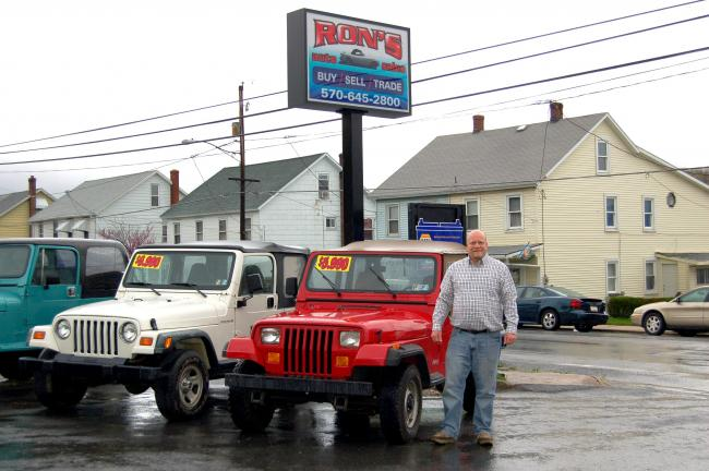 CHRIS PARKER/TIMES NEWS Ron's Auto Sales & Service employee Jeff Bachinski shows off one of the company's vehicles.