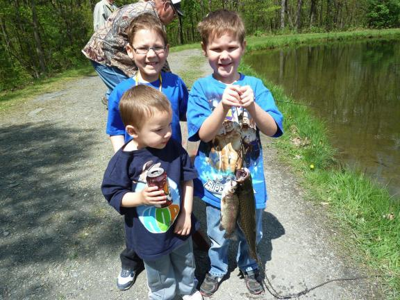 SUSAN LAYLAND/SPECIAL TO THE TIMES NEWS The Imler Brothers, Benjamin and Riley look on as Elija (who is a Dream Come True Kid) proudly holds his first catch of the day.