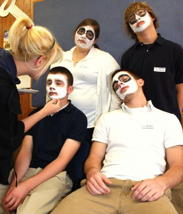 "ANDREW LEIBENGUTH/SPECIAL TO THE TIMES NEWS Samantha Guth, aka Reaper's assistant, makes ""dead"" students for Grim Reaper Day. Students are, front from left, Pete Baddick and Jarred Muffley; back row, Emily Hansler, left, and Joel Kulick."