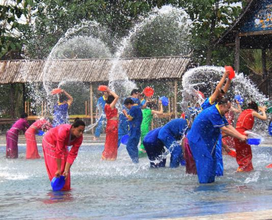 BRANDON TAYLOR/TIMES NEWS Dai residents gather for a re-enactment of a water splashing festival, usually held every April during the Dai's New Year celebrations In Dai culture, water symbolizes purity or the ability to wash away the past and start…