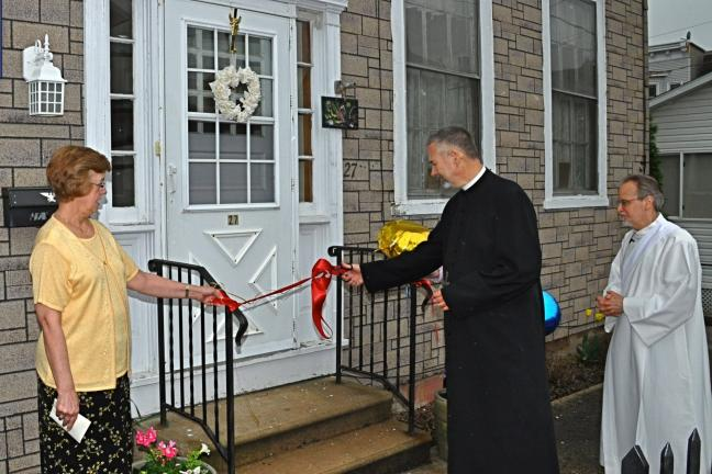 VICTOR IZZO/SPECIAL TO THE TIMES NEWS Looking on as pastor of St. Joseph Catholic Church, Father Francis Baransky, cuts the ribbon officially opening the Mother Pauline Thrift Shop, are Pat Hydro and Deacon Jack Mroz.