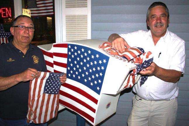 ANDREW LEIBENGUTH/TIMES NEWS Pictured are Tamaqua American Legion chaplain Al Schiano, left, and Master of Ceremonies Ed Smith standing next to their flag collection receptacle located in front of the Tamaqua American Legion.