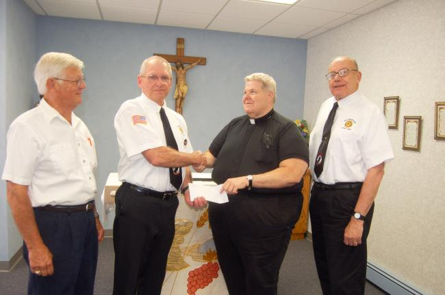 TERRY AHNER/TIMES NEWS  Joe Uhnak, second from left, of the Palmerton United Veteran's Organization receives a donation from the Rev. William Campion, second from right, paster of Sacred Heart Parish Church of Palmerton. Also pictured are Richard…