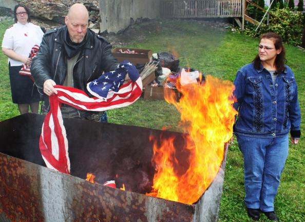 Andy Leibenguth/times news Lansford American Legion Rider Paul Zona, with wife Roseann, Lansford, retires an American flag at the ceremony. Watching in back is Tamaqua Salvation Army Major Sharon Whispell.
