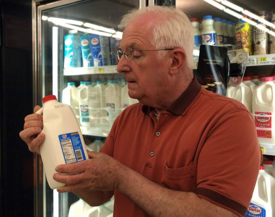 "AL ZAGOFSKY/SPECIAL TO THE TIME NEWS Frank Pasdon, owner of the Jim Thorpe Market, checks ""Sell By"" date on milk container. His employees remove milk that reaches its ""Sell By"" date, which is rare as fresh milk is delivered three times per week."