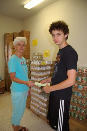 Gail Maholick/TIMES NEWS Matthew Schweitzer, 16, son of Stephen and Debbie Schweitzer of Lehighton, presents proceeds from a benefit concert to Carolyn Long, coordinator of the Lehighton Food Pantry.