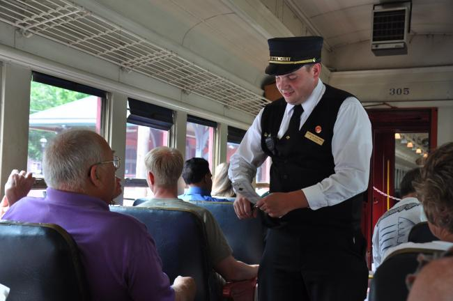 RON GOWER/TIMES NEWS Car attendant Matt Fisher punches tickets for riders on the Pa. Dutch Treat Train of the Lehigh Gorge Scenic Railway, Saturday. The train, with over 250 passengers, traveled from Jim Thorpe to White Haven.