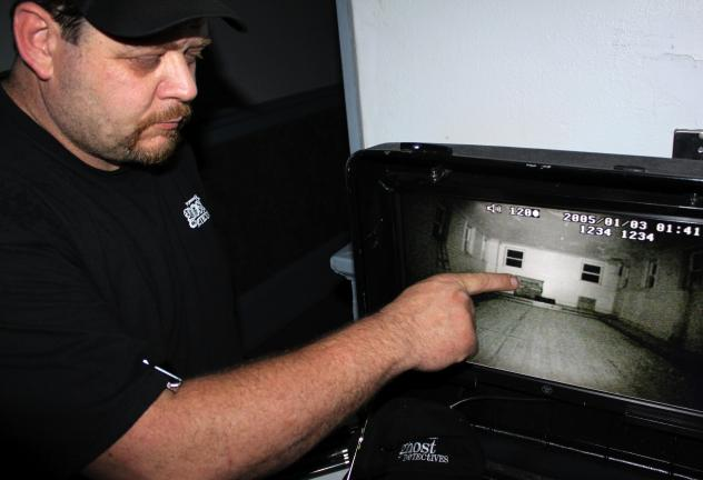 ANDREW LEIBENGUTH/TIMES NEWS Lead investigator and creator of NEPA Paranormal, Bob Christopher, points to floating dust on one of his surveillance monitors. Christopher stated dust is commonly mistaken for paranormal activity.