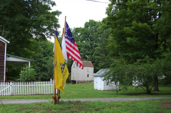 "Four flags were flying at the main intersection of Millbrook Village. They include a Massachusetts (yellow) ""Don't Tread on Me"" flag, a Liberty flag, a U.S. Army flag and the 13-star American flag."