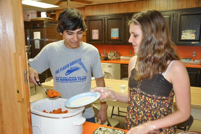 Ron Gower/TIMES NEWS Lehighton Area High School students Marcus Kunkle and Elizabeth Jones serve lunch at Zion United Church of Christ, Lehighton, during free lunch service for LASD students.