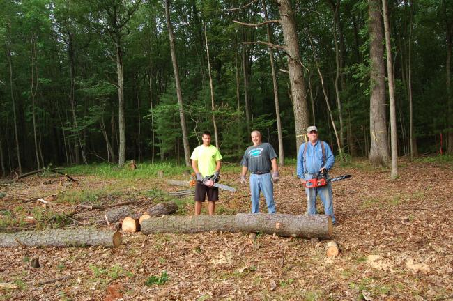 LINDA KOEHLER/TIMES NEWS Left to right, Adam Thieling, NCC student and part-time employee of Chestnuthill Township, Bernie Kozen, Director of West End Park and Open Space Commission and Dave Fleetwood, Chestnuthill Twp. supervisor, are cutting down…