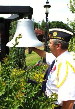 ANDY LEIBENGUTH/TIMES NEWS Pictured ringing the colliery bell 13 times is American Legion's 13th District Deputy Commander Ed Smith.