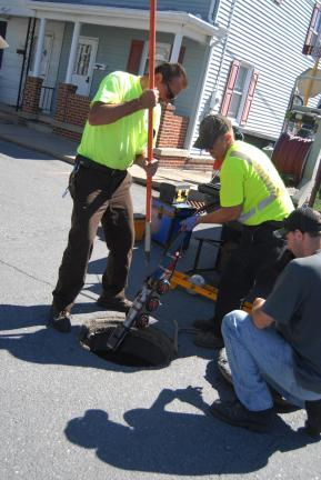 RON GOWER/TIMES NEWS Joe Kosalko, left, Summit Hill workforce supervisor, and Mario Marconi, center, of the Lansford public works department, left special camera into a manhole at Chestnut and Amidon Street in Summit Hill to check sewer lines. At…