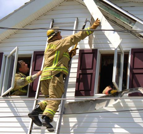 ANDY LEIBENGUTH/TIMES NEWS Firefighters pull off siding to find hot spots and stop the fire from spreading.
