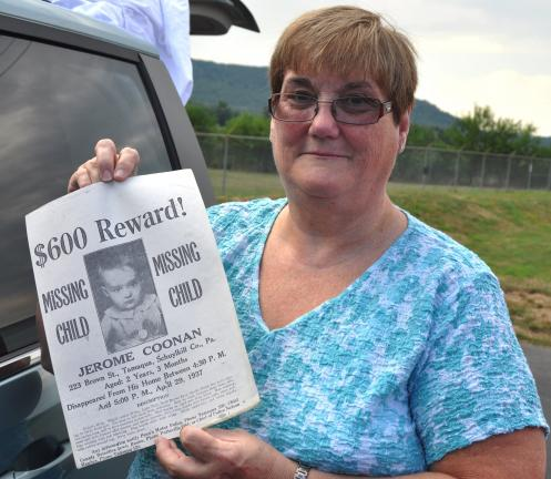 DONALD R. SERFASS/TIMES NEWS  Kathy Coonon Umberger of Lebanon stands at a parking lot near her home Sunday evening and displays a copy of the missing person poster issued by Tamaqua town council in 1937. Her brother, Jerome Coonon, mysteriously…
