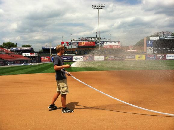 Travis Pitts hoses down the infield before a recent Reading Phillies game. Pitts, a Tamaqua High School graduate and current star member of the Delaware Valley College track team, is doing an internship with the R-Phils this summer.