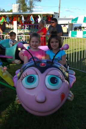 Gail Maholick/TIMES NEWS Jascelyn Mika, 5; and Morgan O'Brien, 4, both of Coaldale, enjoy the kiddie rides on Children's Day at the Carbon County Fair.