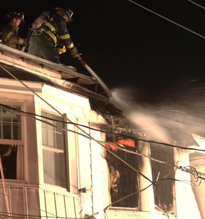 ANDREW LEIBENGUTH/TIMES NEWS It only took 15 minutes last night for firefighters to stop a fast-moving row home fire that started in a third floor bedroom located at 326 East Pine St. in Mahanoy City.