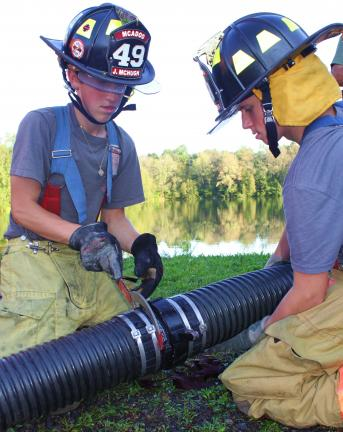 ANDREW LEIBENGUTH/TIMES NEWS McAdoo Fire Company junior firefighters John McHugh, left, and Vinnie Wolf connect their fire truck's water line to the water authority reservoir.