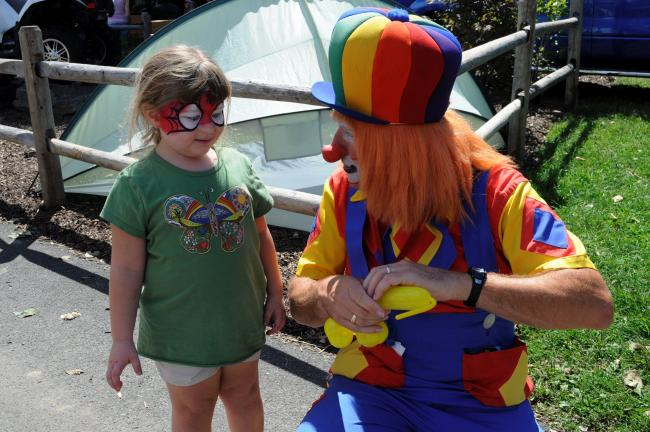 RON GOWER/TIMES NEWS Four-year-old Makayla Frable of Brodheadsville seems to be comparing face makeup with Balloons the Clown at the West End Fair in Gilbert. This is the first year for Balloons, who greets youngsters by giving them balloon…
