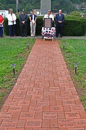 VICTOR IZZO/SPECIAL TO THE TIMES NEWS American Legion Post 360 Commander Thomas Keener speaks at the podium during the dedication on Sunday morning of the Memorial Brick Walkway installed at the Memorial Grounds on Spring Street across the street…
