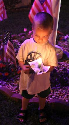 Trent Stair, 3, carefully stares at his vigil candle.