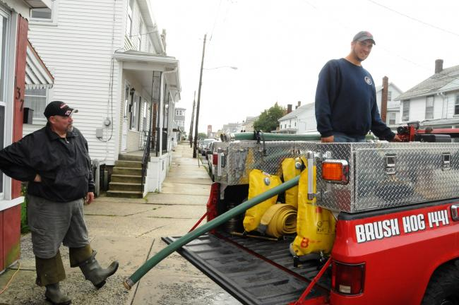RON GOWER/TIMES NEWS Summit Hill Fire Department members Ed Nunemacher, left, and Ronald Yuricheck prepare to pump a basement in the 100 block of East White Street on Thursday. Several homes in the area received backup of sewage from the central…