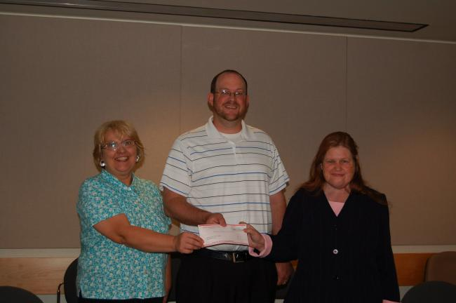 CHRIS PARKER/TIMES NEWS Panther Valley school district business manager Kenneth Marx presents a $4,000 check to Panther Valley Public Library. At left is library board president Marie Ondrus. At right is library director Debi Dodson.